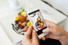Close up of woman picturing food by smartphone. People, holidays, technology, food and lifestyle concept - close up of woman with smartphone taking picture of Royalty Free Stock Image