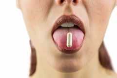 Close-up of woman with pill in mouth Stock Images