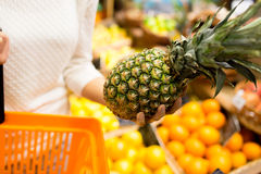 Close up of woman with pineapple in grocery market Stock Photo