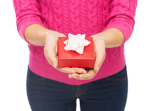 Close up of woman in pink sweater holding gift box Royalty Free Stock Photo