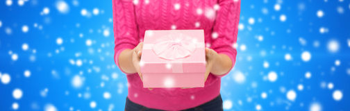 Close up of woman in pink sweater holding gift box Stock Photo