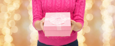 Close up of woman in pink sweater holding gift box Stock Image
