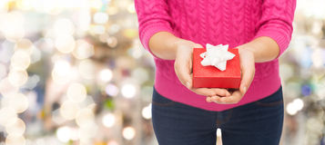 Close up of woman in pink sweater holding gift box Stock Images