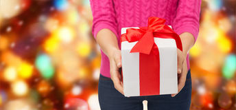 Close up of woman in pink sweater holding gift box Stock Photos