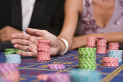 Close up of woman placing bet on roulette table. In casino stock image