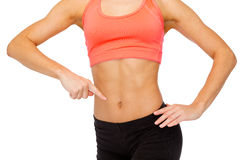 Close up of woman pointing finger at her six pack Royalty Free Stock Photo