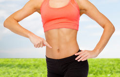Close up of woman pointing finger at her six pack Stock Images