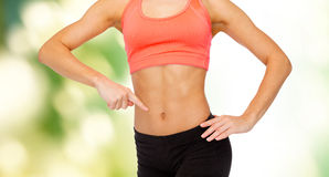Close up of woman pointing finger at her six pack Stock Image