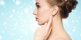 Close up of woman pointing finger to ear over snow Stock Photography