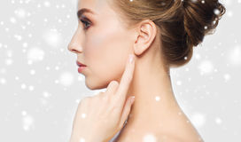 Close up of woman pointing finger to ear over snow Stock Photo