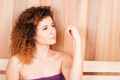 Close-up of woman portrait sitting on bench in sauna Stock Image