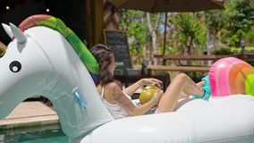 Happy girl in pool drinking a coconut fruit. Close-up of woman portrait smiling and drinking a long cocktail from coconut fruit on exotic island resort stock footage