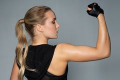 Close up of woman posing and showing biceps in gym. Sport, fitness and people concept - close up of young woman posing and showing muscles in gym stock photo