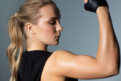 Close up of woman posing and showing biceps in gym. Sport, fitness and people concept - close up of young woman posing and showing muscles in gym stock photography