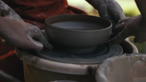 Close-up, Woman Potter Shows Apprentice how to Cut A String Of Clay Products