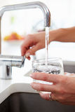 Close Up Of Woman Pouring Glass Of Water From Tap In Kitchen. Close Up Of Woman Pouring Glass Of Water From Metal Tap In Kitchen Stock Image