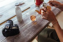 Woman pouring tea in a cup. Close up of a woman pouring tea in a cup from a glass teapot. Woman preparing tea while a professional camera and a bottle filled Royalty Free Stock Photography