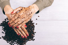 Close-up of a woman puts on hands with red manicure a coffee scr Royalty Free Stock Images