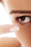 Close up on woman putting lens into eye. Stock Photo