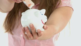 Close up of woman putting money in a piggybank stock video