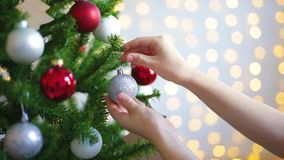 Woman putting ornament on Christmas tree stock footage