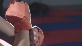 Close up of woman putting on red punching wraps in fitness studio. Slowly stock video