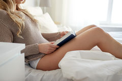 Close up of woman reading book in bed at home Royalty Free Stock Image