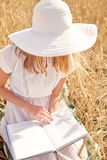 Close up of woman reading book on cereal field Royalty Free Stock Images