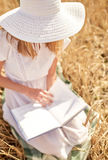 Close up of woman reading book on cereal field Stock Photos