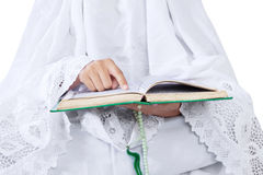 Close-up woman reading Kuran on white. Close-up of woman reading Kuran on white background Royalty Free Stock Image
