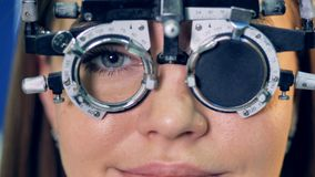 A doctor changes lenses inside a womans trial frame. A close-up on a woman receiving different lenses in her trial frame stock video footage