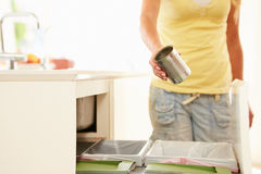 Close Up Of Woman Recycling Kitchen Waste In Bin. Holding Can Stock Image