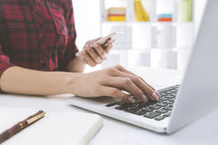 Close up of woman in red checkered shirt is working at her lapto. P keyboard and looking at smartphone. White bookcase with colored folders is seen at the Royalty Free Stock Photo