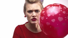 Young blonde woman is threatening to burst the balloon with a needle. Close up of a woman in red dress holding a needle and threatening to burst the balloon with stock video