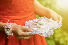 Close-up of a woman in a red dress holding wedding rings Royalty Free Stock Photo