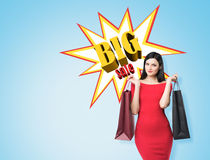 Close up of a woman in red dress with two shopping bags near big Royalty Free Stock Photos
