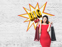Close up of a woman in red dress with two shopping bags near big Stock Image