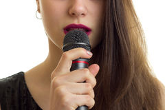 Close up of woman with red lips hold a microphone at her mouth Royalty Free Stock Images