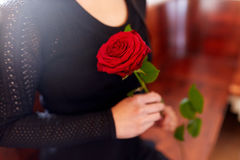 Close up of woman with roses at funeral in church Royalty Free Stock Image