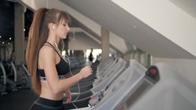 A close up of a woman running on a treadmill. White sneakers shoes sport. Female runner training fast athlete. A close up of a woman running on a treadmill stock video footage