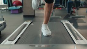 A close up of a woman running on a treadmill fast run. White sneakers shoes sport. Female runner training fast athlete. A close up of a woman running on a stock video