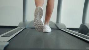 A close up of a woman running on a treadmill. White sneakers shoes sport. Female runner training fast athlete. A close up of a woman running on a treadmill stock video