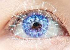 Close-up of woman's blue eye. High Technologies in the futuristi Royalty Free Stock Photo