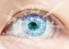 Close-up of woman's blue eye. High Technologies in the futuristi Stock Photos