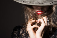 Close-up of a woman's face covered with man's hat Stock Photography