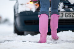 Close up of woman's feet as she pushes car through winter snow Royalty Free Stock Photo
