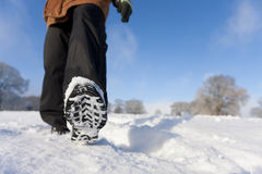 Close up of woman's feet walking through field of snow Royalty Free Stock Images