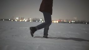Close-up of woman`s feet walking on the snow desert at night . Stabiblized slow-motion shot moon light