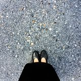Close Up on Woman`s Feet Wearing Black Sandals & Dress, Standing Commemorate on Stone Royalty Free Stock Photo