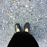 Close Up on Woman`s Feet Wearing Black Sandals & Dress, Standing Commemorate on Stone stock photography